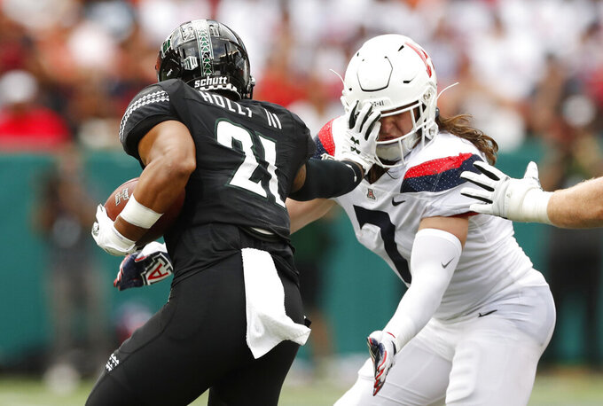 Hawaii running back Fred Holly III (21) stiff -arms Arizona linebacker Colin Schooler (7) during the first quarter of an NCAA college football game Saturday, Aug. 24, 2019, in Honolulu. (AP Photo/Marco Garcia)
