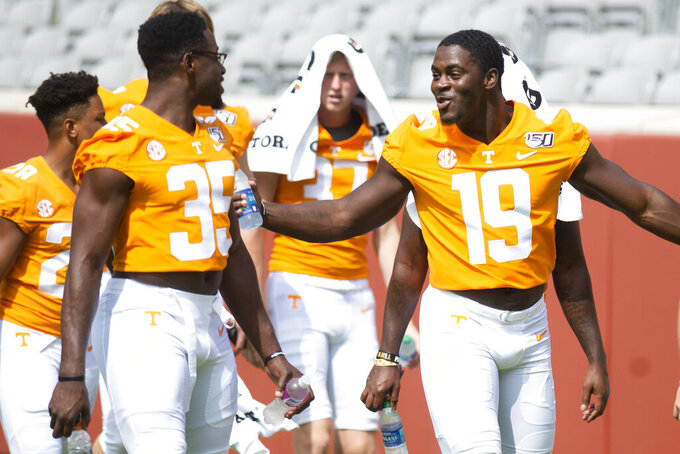 Tennessee linebackers Darrell Taylor (19) and Daniel Bituli (35) talk during Tennessee's NCAA college football Fan Day and team photo shoot in Knoxville, Tenn. Sunday, Aug. 4, 2019. (Saul Young/Knoxville News Sentinel via AP)