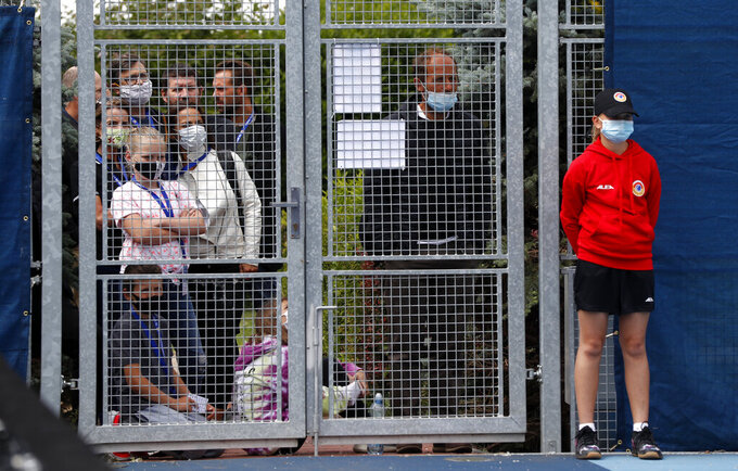 People wearing face masks while standing behind a fence watch the Czech Tennis President's Cup charity tournament final match between Petra Kvitova and Karolina Muchova in Prague, Czech Republic, Thursday, May 28, 2020. The sporting event can take place as the Czech government is taking further steps to ease its restrictive measures adopted to contain the coronavirus pandemic. (AP Photo/Petr David Josek)
