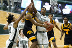 Iowa guard Tony Perkins (11) drives on Michigan State forward Marcus Bingham Jr. (30) in the second half of an NCAA college basketball game in East Lansing, Mich., Saturday, Feb. 13, 2021. (AP Photo/Paul Sancya)