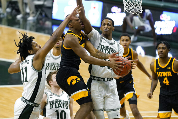 Iowa guard Tony Perkins (11) drives on Michigan State forward Marcus Bingham Jr. (30) in the second half of an NCAA college basketball game in East Lansing, Mich., Saturday, Feb. 13, 2021. (AP Photo/Paul Sancya)