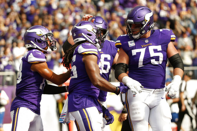 Minnesota Vikings running back Alexander Mattison, center, celebrates with teammates after catching a 15-yard touchdown pass during the first half of an NFL football game against the Detroit Lions, Sunday, Oct. 10, 2021, in Minneapolis. (AP Photo/Bruce Kluckhohn)