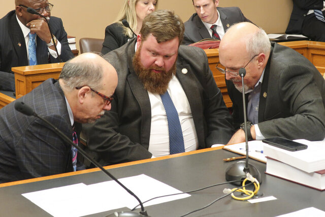 Kansas House Speaker Pro Tem Blaine Finch, center, R-Ottawa, confers with House Minority Leader Tom Sawyer, left, D-Wichita, and Rep. Les Mason, R-McPherson, during talks with senators over extending a state of emergency over the new coronavirus, Wednesday, March 18, 2020, at the Statehouse in Topeka, Kan. Some Republicans are upset with Democratic Gov. Laura Kelly's order to close schools and are looking to curb her power to deal with the pandemic. (AP Photo/John Hanna)