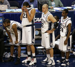 FILE - In this March 26, 2006, file photo, Connecticut players Rashad Anderson, left, Josh Boone (21), Ed Nelson (32), and Craig Austrie (24), watch the game from the sidelines during a loss to George Mason in the fourth round of the NCAA basketball tournament in Washington. George Mason beat Michigan State, North Carolina and Wichita State before taking down No. 1 seed Connecticut and its roster full of NBA talent 86-84 in overtime. They lost 73-58 to eventual national champion Florida in the semifinals. (AP Photo/Susan Walsh, File)