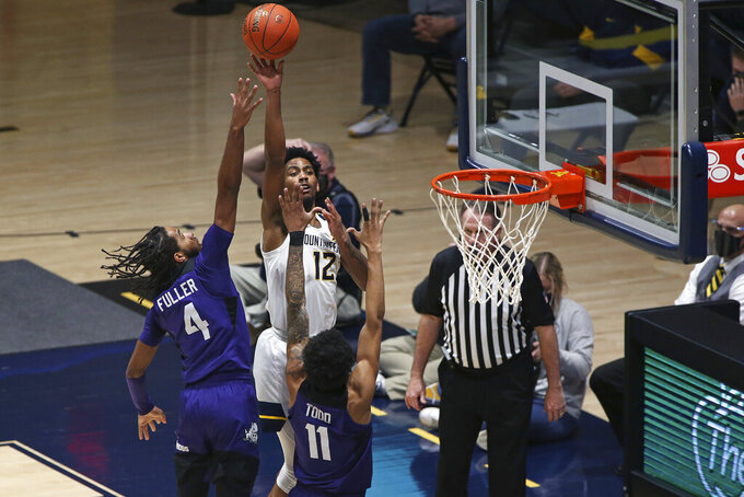 West Virginia guard Taz Sherman (12) shoots while defended by Texas Christian guards PJ Fuller (4) and Taryn Todd (11) during the second half of an NCAA college basketball game Thursday, March 4, 2021, in Morgantown, W.Va. (AP Photo/Kathleen Batten)