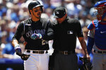 Colorado Rockies' Nolan Arenado, left, reacts after getting hit by a pitch from Chicago Cubs starting pitcher Cole Hamels as home plate umpire Roberto Ortiz and catcher Victor Caratini look on in the third inning of a baseball game Wednesday, June 12, 2019, in Denver. (AP Photo/David Zalubowski)