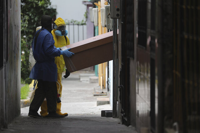 Funeral workers remove the body of a person who is suspected to have died from symptoms related to the new coronavirus, in Quito, Ecuador, Friday, Aug. 14, 2020. The numbers of those infected with COVID-19 have been rising in the capital. (AP Photo/Dolores Ochoa)