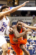 Clemson's Elijah Thomas, right, cradles the ball as he drives past Pittsburgh's Terrell Brown (21) on his way to the basket during the first half of an NCAA college basketball game, Wednesday, Feb. 27, 2019, in Pittsburgh. (AP Photo/Keith Srakocic)
