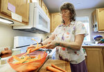 In this Aug. 22, 2018 photo, April Box prepares carrots and squash for dinner, at her home in Spokane, Wash. Millions of people covered under the Affordable Care Act will see only modest premium increases next year, and some will get a price cut. That's the conclusion from an exclusive analysis of the besieged but resilient program that still divides voters heading into this year's midterm elections. (AP Photo/Ted S. Warren)
