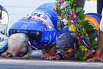 Takuma Sato, right, of Japan, and car owner David Letterman, left, kiss the yard of bricks on the start-finish line after Sato won the Indianapolis 500 auto race at Indianapolis Motor Speedway in Indianapolis, Sunday, Aug. 23, 2020. (AP Photo/Michael Conroy)