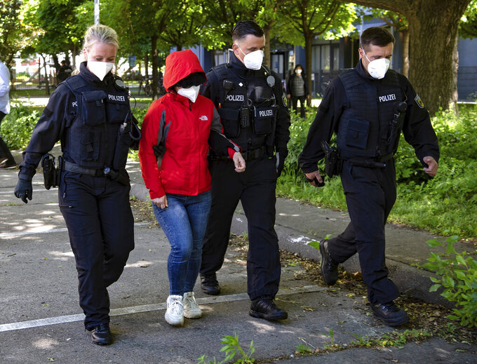 Police officers lead a woman to a vehicle during a raid against a group of people suspect to brought Vietnamese people to Europe on fraudulently obtained visas, in Berlin, Germany, May 31, 2021. Authorities say suspects have been arrested in Germany and Slovakia in raids on a group accused of smuggling Vietnamese people into Germany and other European countries for large fees that they had to work off in massage parlors and brothels among other places. (Paul Zinken/dpa via AP)