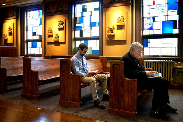 In this Wednesday, March 25, 2020, photo Bishop David Zubik, right front, of the Catholic Diocese of Pittsburgh, seminarian Erik Pintar and others attend a mid-day prayer at the St., Paul Seminary in East Carnegie, Pa. Bishop Zubik called on Catholics in the Diocese of Pittsburgh to mark Wednesday as a day of prayer for those affected by the coronavirus.  (Nate Guidry/Pittsburgh Post-Gazette via AP)