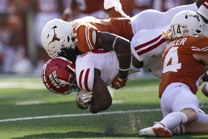 Louisiana-Lafayette running back Emani Bailey (9) is hit by Texas linebacker DeMarvion Overshown (0) during the second half of an NCAA college football game Saturday, Sept. 4, 2021, in Austin, Texas. (AP Photo/Eric Gay)