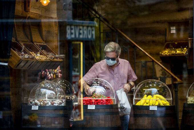 A man wearing a face mask to prevent the spread of coronavirus buys sweets in downtown Madrid, Spain, Wednesday, Sept. 16, 2020. The Spanish capital will introduce selective lockdowns in urban areas where the coronavirus is spreading faster, regional health authorities announced on Tuesday. (AP Photo/Manu Fernandez)