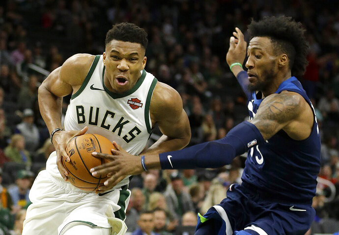 Milwaukee Bucks' Giannis Antetokounmpo, left, drives to the basket against Minnesota Timberwolves' Robert Covington during the first half of a preseason NBA basketball game Thursday, Oct. 17, 2019, in Milwaukee. (AP Photo/Aaron Gash)