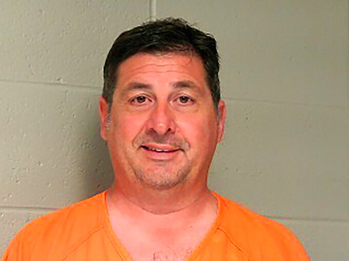 In this booking photo provided by the Woodford County Jail shows Lawrence County Attorney Michael Hogan, who was arrested on Tuesday, June 8, 2021. Hogan, a Kentucky prosecutor who twice ran for statewide office was indicted on wire fraud charges stemming from an alleged scheme that funneled more than $365,000 from a delinquent tax account into personal accounts, federal prosecutors said Tuesday. The indictment charged Hogan and his wife Joy Hogan with one count of conspiracy to commit wire fraud. (Woodford County Jail via AP)