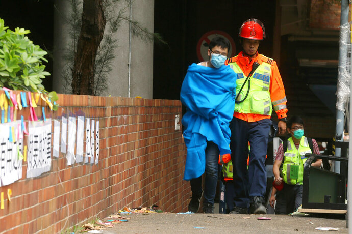 A medical worker walks with an injured protester at Hong Kong Polytechnic University in Hong Kong, Tuesday, Nov. 19, 2019. About 100 anti-government protesters remained holed up at the university Tuesday as a police siege of the campus entered its third day. (AP Photo/Achmad Ibrahim)