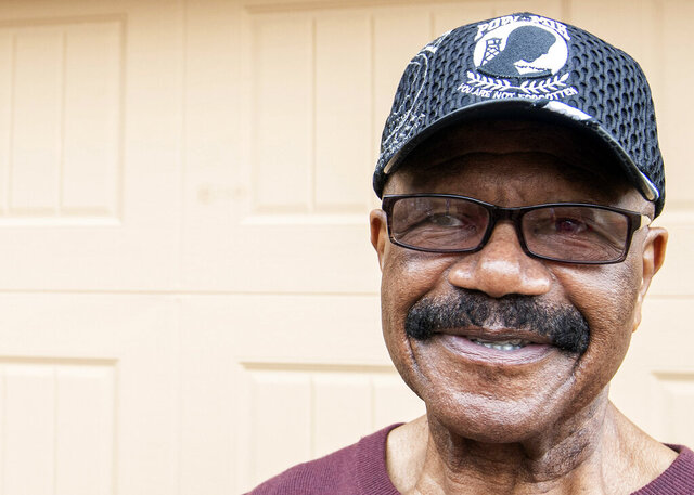 In this Thursday, Dec. 26, 2019, photo, Memphis native, Lt. Col. James Williams, who was a prisoner of war in Vietnam poses for a portrait in front of his sister's home in Cordova, Tenn. Williams and other veterans returned to Hanoi, Vietnam, to gain closure from their time at war. Williams connected with a Valor Administration representative who notified him of the trip to Vietnam, a golden opportunity to complete part of his living list. (Ariel Cobbert/The Commercial Appeal via AP)