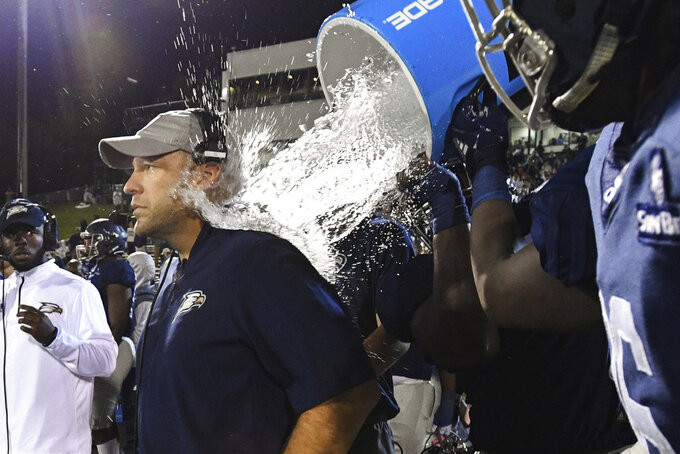 Georgia Southern head coach Chad Lunsford gets doused as an NCAA college football game against Appalachian State comes to a close, Thursday, Oct. 25, 2018, in Statesboro, Ga. Georgia Southern won 34-14. (AP Photo/John Amis)