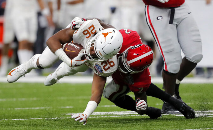 Texas running back Keaontay Ingram (26) is brought down by Georgia defensive back Richard LeCounte (2) during the first half of the Sugar Bowl NCAA college football game in New Orleans, Tuesday, Jan. 1, 2019. (AP Photo/Gerald Herbert)