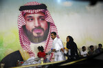 A Saudi family walk past a giant poster of Saudi Crown Prince Mohammed bin Salman, at a shopping mall in  Jiddah, Saudi Arabia, Sunday, Sept. 15, 2019. The weekend drone attack on one of the world's largest crude oil processing plants that dramatically cut into global oil supplies is the most visible sign yet of how Aramco's stability and security is directly linked to that of its owner -- the Saudi government and its ruling family. (AP Photo/Amr Nabil)