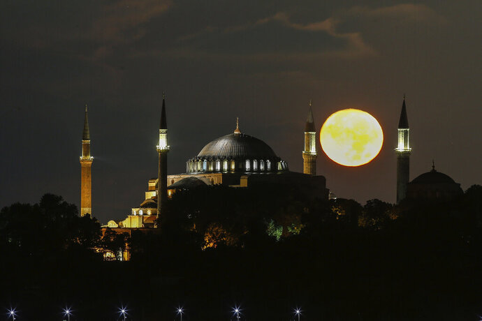 The full moon rises behind the Byzantine-era Hagia Sophia, in the historic Sultanahmet district of Istanbul, early Tuesday, Sept. 1, 2020. Worshipers held the first Muslim prayers in 86 years inside the Istanbul landmark that served as one of Christendom's most significant cathedrals, a mosque and a museum before its conversion back into a Muslim place of worship on July 24, 2020. The conversion of the edifice, has led to an international outcry. (AP Photo/Emrah Gurel)