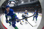 Vancouver Canucks' Tim Schaller, front left, plays the puck around the boards away from St. Louis Blues' Zach Sanford, center, during the first period of an NHL hockey game Tuesday, Nov. 5, 2019, in Vancouver, British Columbia. (Darryl Dyck/The Canadian Press via AP)