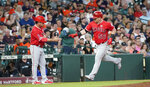Los Angeles Angels' Kole Calhoun (56) is congratulated by third base coach Mike Gallego after hitting a two-run home run against the Houston Astros during the third inning of a baseball game Friday, July 5, 2019, in Houston. (AP Photo/David J. Phillip)