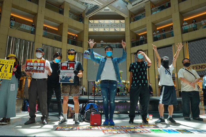 Protesters gather at a shopping mall in Central during a pro-democracy protest against Beijing's national security law in Hong Kong, Tuesday, June 30, 2020. Hong Kong media are reporting that China has approved a contentious law that would allow authorities to crack down on subversive and secessionist activity in Hong Kong, sparking fears that it would be used to curb opposition voices in the semi-autonomous territory. The placard, second from left, reads: