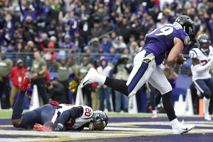 Baltimore Ravens tight end Mark Andrews (89) catches a touchdown pass from quarterback Lamar Jackson, not visible, as Houston Texans strong safety Justin Reid (20) falls while trying to make a diving stop in the end zone during the first half of an NFL football game, Sunday, Nov. 17, 2019, in Baltimore. (AP Photo/Gail Burton)