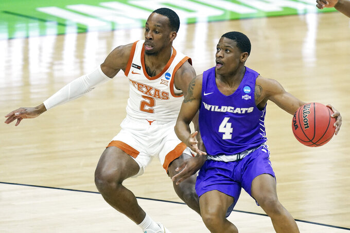 Abilene Christian's Damien Daniels (4) drives against Texas' Matt Coleman III (2) during the first half of a college basketball game in the first round of the NCAA tournament at Lucas Oil Stadium in Indianapolis Saturday, March 20, 2021. (AP Photo/Mark Humphrey)