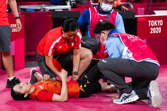Singapore's Yu Mengyu receives medical treatment during her table tennis women's singles semifinal match against China's Chen Meng at the 2020 Summer Olympics, Thursday, July 29, 2021, in Tokyo. (AP Photo/Kin Cheung)