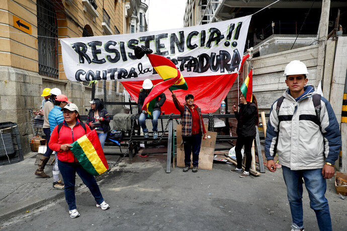 Anti-government protesters block a street meters away from the presidential palace in La Paz, Bolivia, Sunday, Nov. 10, 2019. President Evo Morales is calling for new presidential elections and an overhaul of the electoral system Sunday after a preliminary report by the Organization of American States found irregularities in the Oct. 20 elections. (AP Photo/Juan Karita)