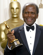 FILE - Sidney Poitier poses with his honorary Oscar trophy during the 74th annual Academy Awards in Los Angeles on March 24, 2002.  Arizona State University has named its new film school after Poitier. The university, which is expanding its existing film program into its own school, says it has invested millions of dollars in technology to create one of the largest, most accessible and most diverse film schools. The Sidney Poitier New American Film School will be unveiled at a ceremony on Monday, Jan. 25, 2021. (AP Photo/Doug Mills, File)