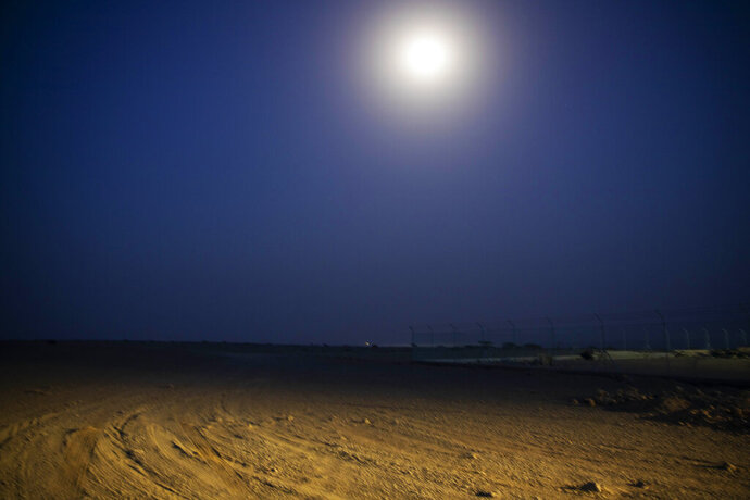 In this July 14, 2019 photo, the moon shines on the beach where smugglers move Ethiopian migrants on pick up trucks to take them on a boat to Yemen, in Obock, Djibouti. Over the past three years, the IOM reported 9,000 Ethiopians were deported each month. Many migrants have made the journey multiple times in what has become an unending loop of arrivals and deportations. (AP Photo/Nariman El-Mofty)