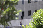 FILE - In this June 7, 2017, file photo, a man hands a child to a security guard from Iran's parliament building after an assault of several attackers, in Tehran, Iran. Iran said Saturday, July 7, 2018, it executed eight people convicted in the 2017 Islamic State group attack on parliament and the shrine of Ayatollah Ruhollah Khomeini in Tehran. (Omid Vahabzadeh/Fars News Agency via AP, File)