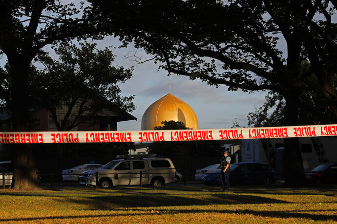 FILE - In this March 17, 2019, file photo a police officer stands guard in front of the Masjid Al Noor mosque in Christchurch, New Zealand, where one of two mass shootings occurred. Facebook will work with law enforcement organizations to train its machine learning technology to recognize videos of violent events as part of a broader effort to crack down on extremism. The move comes after its artificial intelligence did not detect the first-person video of a terrorist attack on the mosque in Christchurch. (AP Photo/Vincent Yu, File)