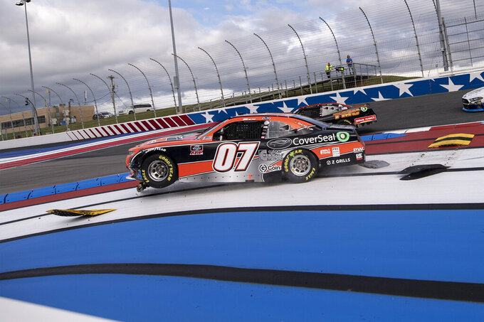 NASCAR Xfinity Series driver Josh Bilicki (07) runs over a curb strip and wrecks during the NASCAR Xfinity auto racing race at the Charlotte Motor Speedway Saturday, Oct. 9, 2021, in Concord, N.C. (AP Photo/Matt Kelley)