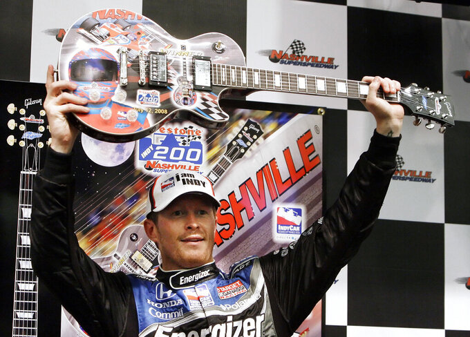 FILE - In this July 12, 2008, file photo, Scott Dixon, of New Zealand, holds his guitar trophy after winning the rain-shortened IndyCar Series auto race in Gladeville, Tenn. The IndyCar series race will be held in downtown Nashville, Tenn., this weekend. (AP Photo/Mark Humphrey, File)