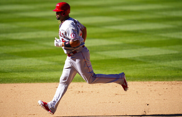 Los Angeles Angels' Albert Pujols circles the bases after hitting a two-run home run off Colorado Rockies relief pitcher Carlos Estevez in the eighth inning of a baseball game Sunday, Sept. 13, 2020, in Denver. (AP Photo/David Zalubowski)