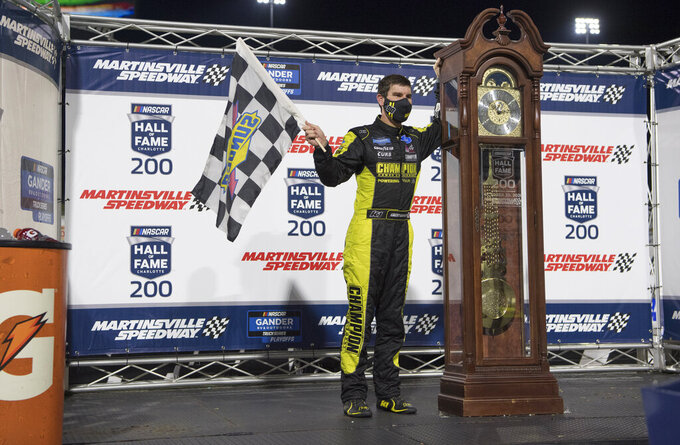 Grant Enfinger stands next to the trophy after winning the NASCAR Truck Series auto race at Martinsville Speedway in Martinsville, Va., Friday, Oct. 30, 2020. (AP Photo/Lee Luther Jr.)