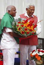 Karnataka state Governor Vajubhai Vala, right, presents a bouquet to Bharatiya Janata Party (BJP) leader B. S. Yeddyurappa after the latter was sworn in as Chief Minister of the state in Bangalore, India, Thursday, May 17, 2018. The elections in India's southern state of Karnataka were held on last Saturday. (AP Photo/Aijaz Rahi)
