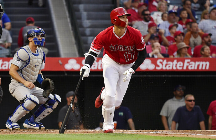 Los Angeles Angels' Shohei Ohtani watches his solo home run next to Los Angeles Dodgers catcher Austin Barnes during the first inning of a baseball game Tuesday, June 11, 2019, in Anaheim, Calif. (AP Photo/Mark J. Terrill)