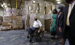 Texas Gov. Greg Abbott, left, and other officials visit a Texas Division of Emergency Management Warehouse filled with Personal Protective Equipment, Tuesday, Aug. 4, 2020, in San Antonio. (AP Photo/Eric Gay)