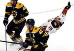 Anaheim Ducks center Ryan Getzlaf (15) falls back after chasing the puck against Boston Bruins defenseman Matt Grzelcyk (48) and right wing David Backes (42) in the first period of an NHL hockey game, Thursday, Dec. 20, 2018, in Boston. (AP Photo/Elise Amendola)