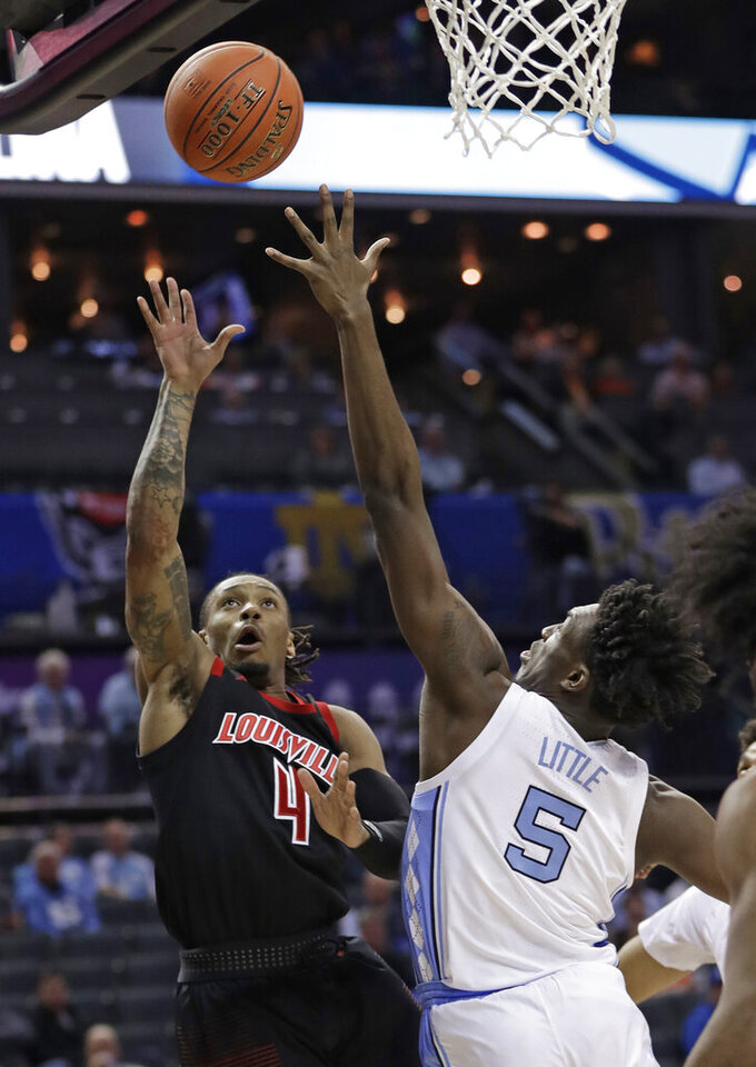 Louisville's Khwan Fore (4) shoots over North Carolina's Nassir Little (5) during the first half of an NCAA college basketball game in the Atlantic Coast Conference tournament in Charlotte, N.C., Thursday, March 14, 2019. (AP Photo/Nell Redmond)