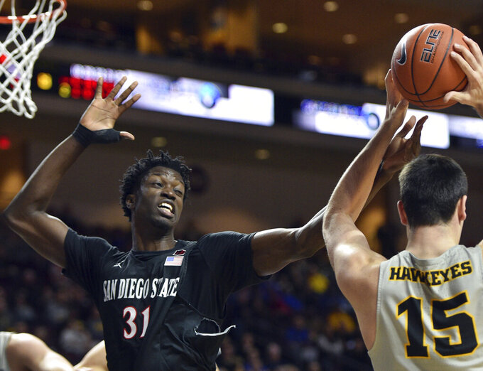 San Diego State forward Nathan Mensah (31) defends against Iowa forward Ryan Kriener (15) during the second half of an NCAA college basketball game Friday, Nov. 29, 2019, in Las Vegas. (AP Photo/David Becker)