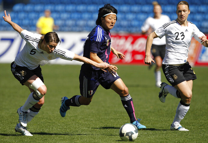In this March 7, 2012, file photo, Japan's Yuki Nagasato, center, challenges Germany's Annike Krahn, left, and Josephine Henning during the Algarve Cup women's soccer final match at the Algarve stadium outside Faro, southern Portugal. Nagasato won the Women's World Cup with Japan in 2011 and currently plays for the Chicago Red Stars in the NWSL. Now she is joining the Japanese men's club Hayabusa Eleven on loan. (AP Photo/Armando Franca, File)