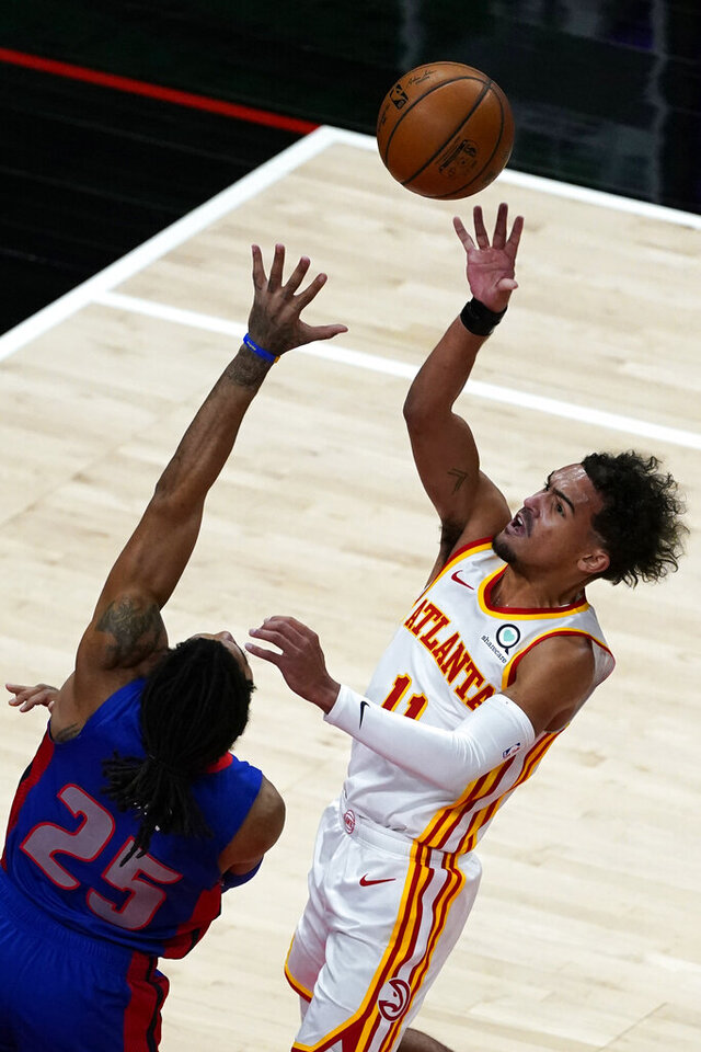 Atlanta Hawks guard Trae Young (11) shoots as Detroit Pistons guard Derrick Rose (25) defends during the first half of an NBA basketball game Wednesday, Jan. 20, 2021, in Atlanta. (AP Photo/John Bazemore)