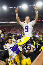 LSU quarterback Joe Burrow (9) is carried off the field by teammates Tyler Shelvin (72) and Zach Von Rosenberg (38) after defeating Alabama 46-41 in an NCAA college football game, Saturday, Nov. 9, 2019, in Tuscaloosa , Ala. (AP Photo/John Bazemore)